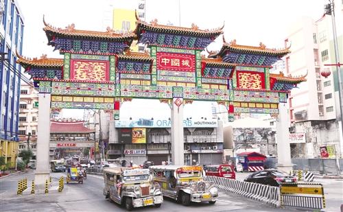 亚洲性爱城论坛_图为在菲律宾首都马尼拉,两辆公交车从中国城的牌匾下驶过. 新华社发
