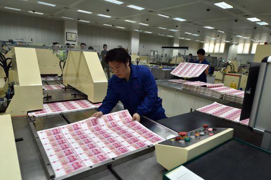 北京印钞有限公司工作人员将印制完成的大张新版百元钞票摆放在机器上进行切割(10月29日摄)。