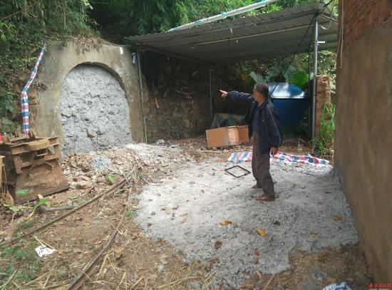 坑美村乡民向记者指认方才被封堵的矿口。