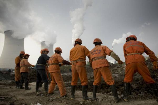 上海,电信工人在开挖光缆水沟,暗地里是吴泾发电厂的冷却塔与烟囱。徐晓林 磅礴材料