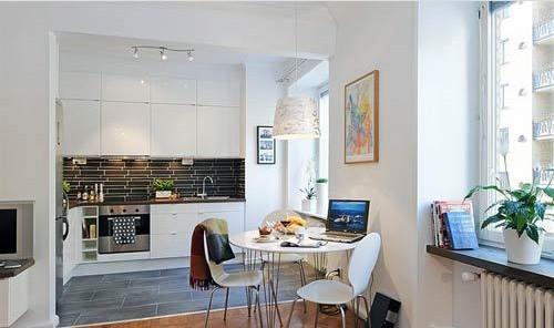 餐桌餐椅放置在客厅和厨房的衔接地带,他们的设计依然很简约很漂亮,白色的外观让人喜爱。墙上的装饰画很好看,还有头顶上的吊灯设计实在精美。