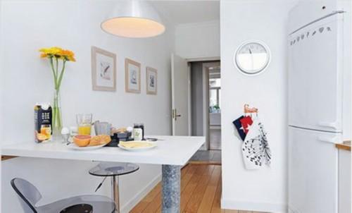 餐桌的设计属于典型的小户型设计,其实就是墙边延伸的一块板,再配上了一个桌脚。高脚凳的餐椅很有现代的气息,也很时尚。
