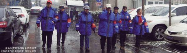 丰台区市民劝导队队员在雨雪交加的天气仍坚持巡逻,保社区平安
