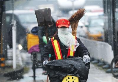 昨日北京迎来第二场雪,方庄街头,一位环卫工人雪中骑车。新京报记者 尹亚飞 摄
