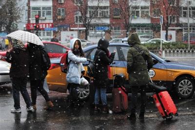 昨日上午9时许,大雪如鹅毛,南三里屯路几位路人等待出租车。新京报记者 薛珺 摄
