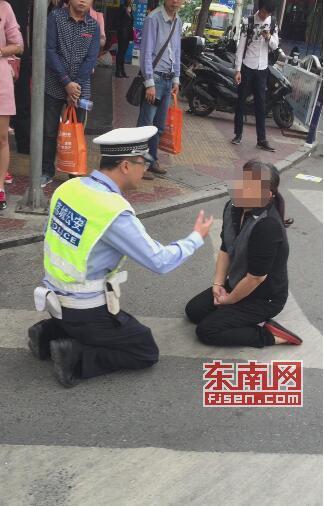 妇女闯红灯被拦即跪又躺耍无赖 交警跪地求沟通