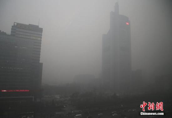 11月30日,北京电视台大楼在雾霾中若隐若现。当日,北京现空气重污染过程,这是自今年3月31日《北京市空气重污染应急预案》修订后,首次启动橙色级别的预警,也是今年首个空气重污染橙色预警。中新社记者 张浩 摄