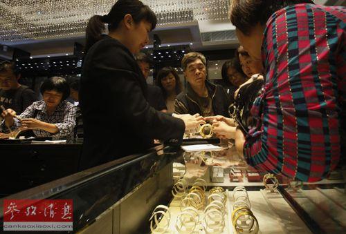 香港一家珠宝店的伙计在向主顾采购金手镯。(材料图像)