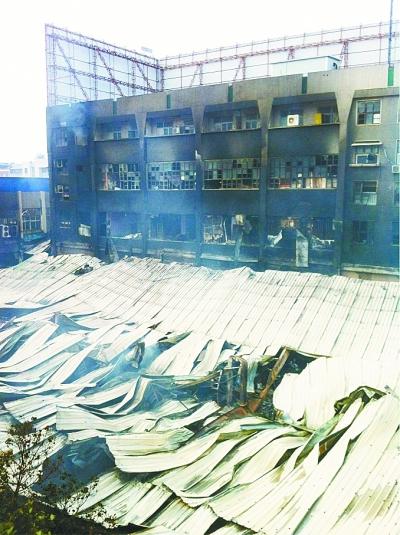 超市的铝合金顶篷被大火烧塌。记者杨涛 摄