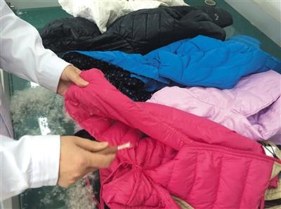 中国纺织工业联合会检测中心实验人员正在拆取羽绒服样品的填充物。
