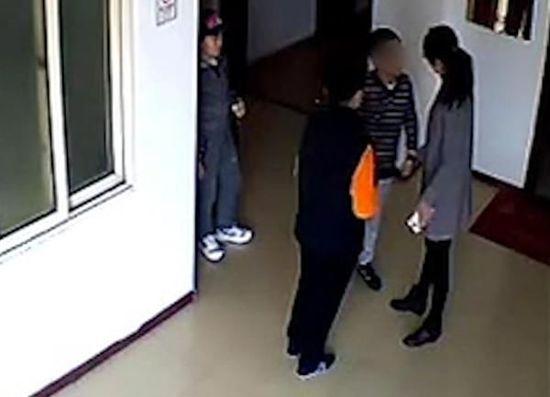 监控显示,寇某按住小宇,教唆儿子对其进行殴打。