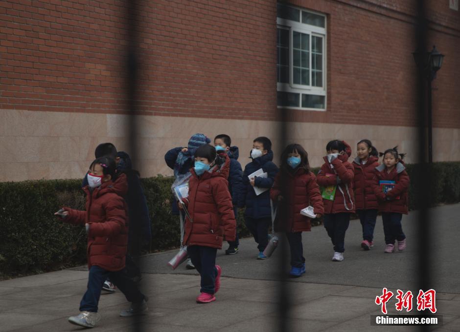 北京市海淀外国语实验学校的学生在教师的带领下前往室内活动.中新图片
