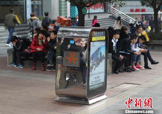 图为泛滥市民坐在智能废物桶旁的花坛边休憩和玩手机。 周毅 摄
