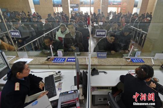 材料图:11月26日,山西太原火车站售票大厅,作业人员在向游客出售车票。 中新社记者 武豪杰 摄