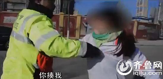男子挥拳想打落民警手中的法律记载仪,并用头撞向交警。(视频截图)