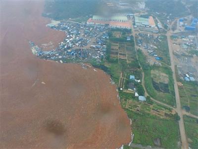 2015年12月20日航拍的事故现场。红褐色泥土包围建筑。新华社发