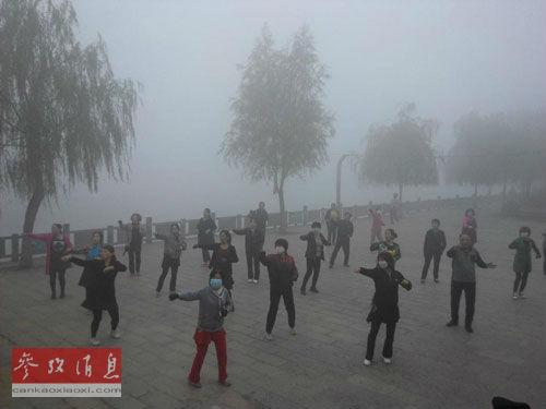 资料图片:为防御雾霾,中国人戴口罩晨练。