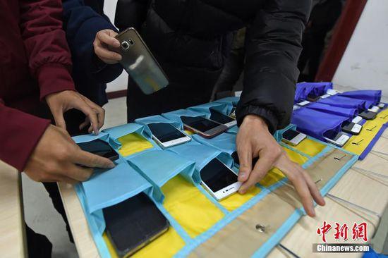 """12月21日,山西太原理工大学教室内,上课学生将各自的手机放入前排的收纳袋中,集中精力听课学习。据该校老师介绍,""""无手机课堂""""旨在倡导同学们提高在课堂上的学习效率,减少对手机的依赖程度,养成合理使用手机的好习惯<b"""