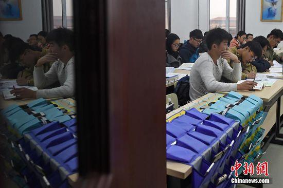 """12月21日,山西太原理工大学教室内,上课学生将各自的手机放入前排的收纳袋中,集中精力听课学习。据该校老师介绍,""""无手机课堂""""旨在倡导同学们提高在课堂上的学习效率,减少对手机的依赖程度,养成合理使用手机的好习惯。武俊杰"""