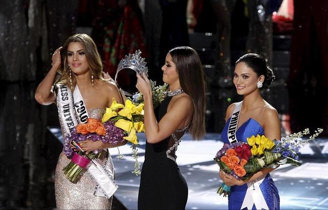 """20日,上届""""环姐""""、来自哥伦比亚的保利娜・维加(中)正为真正的2015年环球小姐、菲律宾佳丽武茨巴赫(右)佩戴桂冠。此前,因主持人口误,保利娜一度将桂冠戴在了""""老乡""""阿里亚德娜・古铁雷斯(左)头上。"""