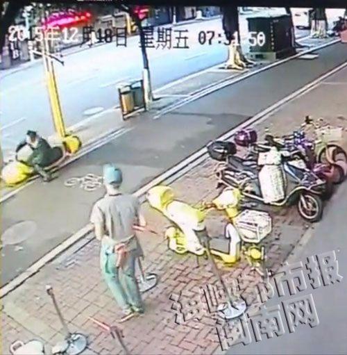 陈先生刚出店,没走两步,路过的这辆电动车突然摔倒,他赶紧过去帮忙扶起来(视频截图)