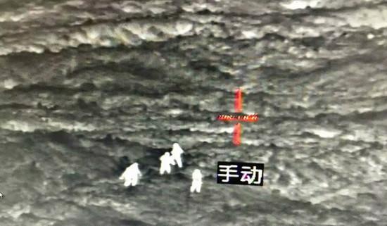 在热成像摄像头的指引下,工程人员在被掩埋房屋上方放置标记物。中青网图