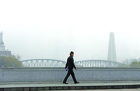今天,路上的行人全部武装。在乍浦路桥上瞭望浦东,只见雾不见楼。 /晨报记者 殷立勤