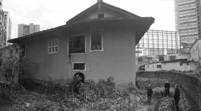 22日下午,赖伍江(中)和弟弟赖伍豪(右)、赖伍钦站在自家院内。京华时报记者 怀若谷 摄