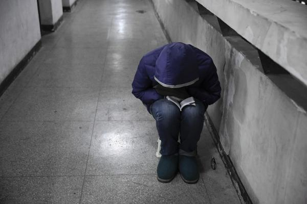 一名考研学子坐在教学楼的走廊上,借助微弱的灯光做最后的复习。 东方IC 资料