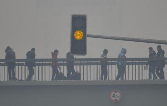 2015年11月8日,沈阳,人们走在严重污染的天气里,街头黄色信号灯不断闪烁。