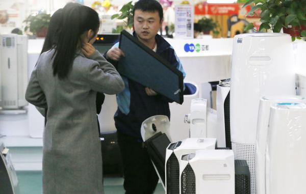 """12月13日,北京,频仍的雾霾气候,使氛围污染器成为都城家电商场的""""骄子""""。 视觉国家 图"""