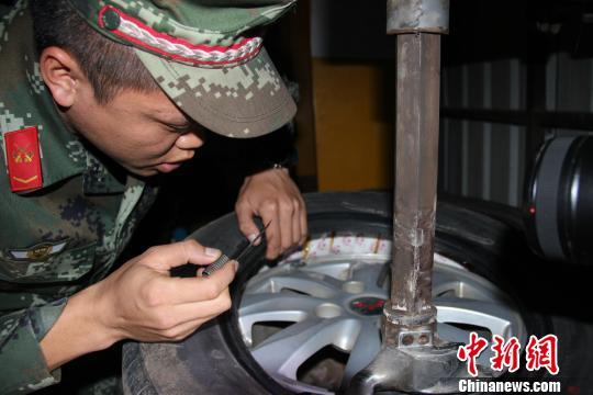 图为边防官兵在微型车的轮胎中发现毒品可疑物。 万霜降 摄