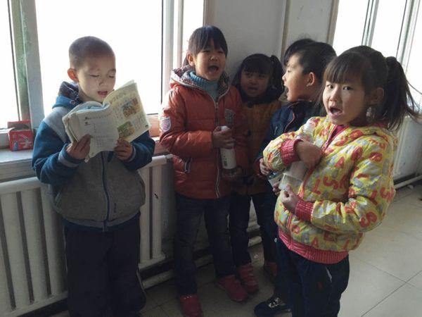 坤坤(左一)在阅读课文