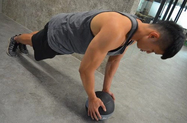 身体伏地向下,手肘弯至90度后即可撑起。撑起时手肘微弯不锁死。(尽量把篮球充足气,以免发生危险)