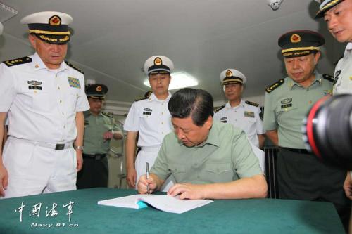 图为2013年9月1日,习近平观看舰载机滑跃起飞,在辽宁舰上为官兵签名留念。