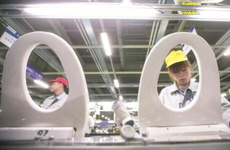 """2015年被疯抢的日本马桶盖,引发了各界的关注和思考,甚至将它和""""供给侧结构性改革""""联系起来。图为2015年3月,浙江杭州,某公司,工人们正在生产被疯抢的""""日本马桶盖""""。CFP"""