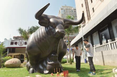 """2015年,中国股民坐了一把过山车。上图为2015年3月17日,广东省中山市某证券营业部,一名阿姨带着熟睡的孙子炒股。下图为2015年8月24日,福建省厦门市一个""""牛骑熊""""雕塑前,一些股民专程过来上香,祈求股票大涨。CFP"""