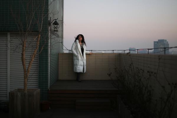 翟永明裹起白色的羽绒服,孑然立在画卷一般的暮色里。澎湃新闻记者 权义 图