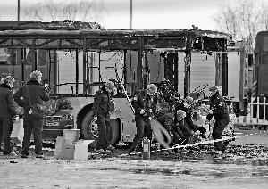 5日,警察在公交车起火事故现场勘察。公交车被烧只剩下一个铁架子。新华社发