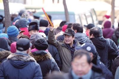 一名市民兴奋地举起抢到的邮册。京华时报记者谭青摄