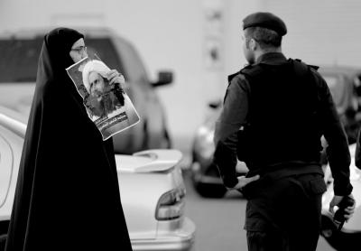 1月4日,在巴林首都麦纳麦郊区,一名巴林妇女手举知名什叶派教士奈米尔头像与警察对峙。新华社发