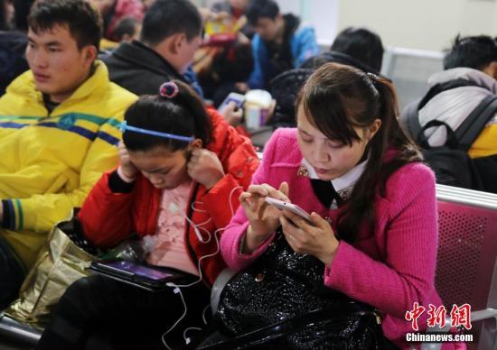 资料图:使用手机的人们。刘真珍