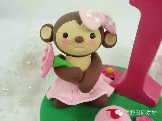 在纸杯蛋糕上,覆盖一个机敏可爱的小猴子