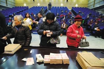1月7日,顺义区公民法院正在为80名白叟发放追缴回去的上当金钱。新京报记者 李飞 摄