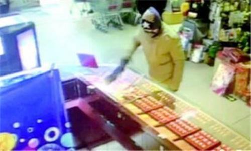 8日晚7点24分,一上身穿浅绿色棉衣,头带线帽、脸带口罩的男子,用随身携带的锤子敲击超市的首饰柜台,抢走黄金首饰后迅速逃逸。(视频截图)