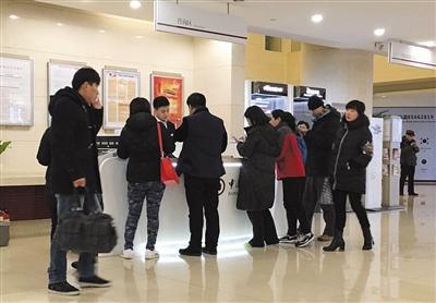 1月11日,在一家银行的自动换汇机周围,前来咨询相关业务的客户。新京报记者 陈杨 摄