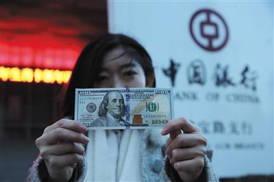 1月11日,一位市民手举刚从银行用人民币兑换出来的美元拍照。新京报记者 卢淑婵 摄