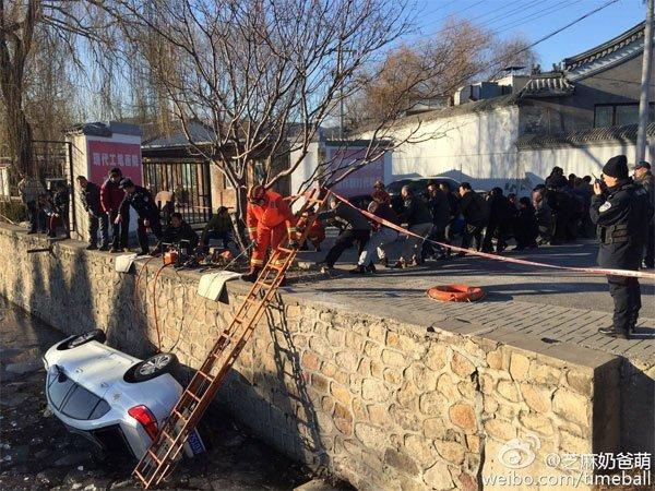 事发觉场,消防队员和途经大众一同拉坠河轿车。图像来历于收集