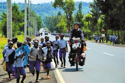 在乌干达,下学的孩儿们追着杜风彦的自行车一同跑。 受访者供图