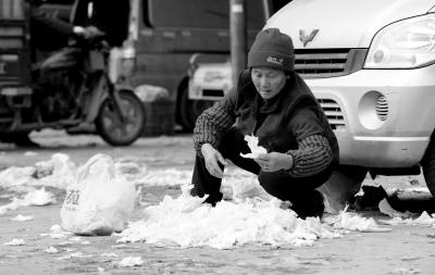 来自四川广元的农夫工岳中兰在郑州的一个菜商场捡菜叶(1月12日摄)。新华社发